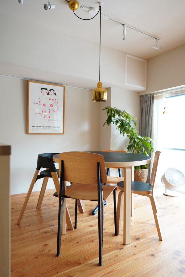 アルヴァ・アアルトがデザインした照明「ゴールデンベル」やこだわりの家具、ポスターが自然素材の空間と調和している。