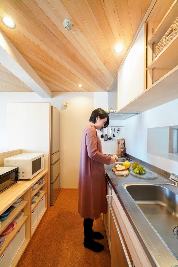 ダイニングから見えない位置に家電が収まる木製の造作キッチン。