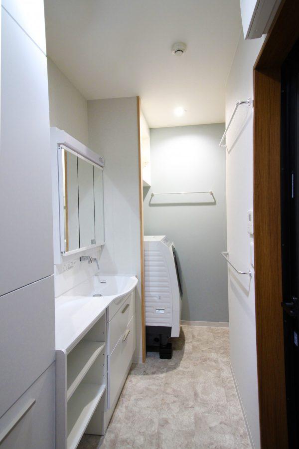 白を基調にした洗面所、突き当り壁のグレーが良いアクセントに