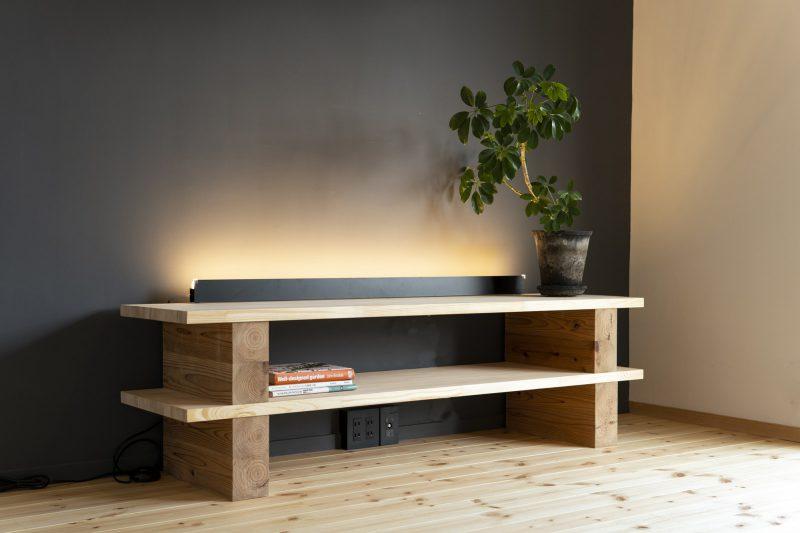 オリジナルのテレビボードは柱材と板材をシンプルに構成。目に優しい灯を配置し、アクセントウォールを強調。